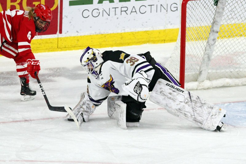 Abigail Levy of Minnesota State makes a save at the side of the net with Wisconsin's Presley Norby fighting for the puck in front of her. (David Faulkner, SPX Sports)
