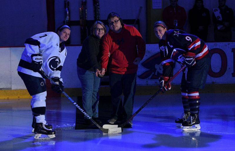 Mary Ellen Greacen, Director of Operations at the Autism Society of Pittsburgh, and her son, Alec, drop the puck for a ceremonial faceoff between Penn State captain Kelsey Crow and Robert Morris captain Maggie LaGue before the Colonials' third annual Teddy Bear Toss game. (Justin Berl/RMU Athletics)