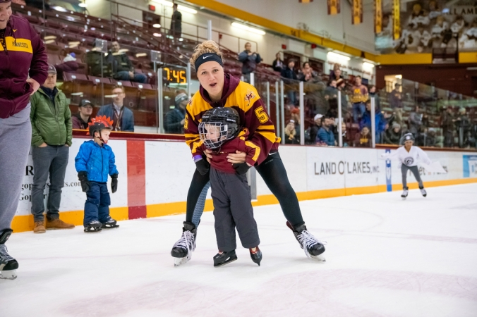 Sophie Skarzynski helps a young fan at the Skate with the Gophers event. (Brad Rempel/Gopher Athletics)