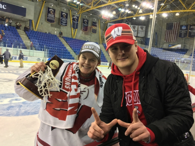 """Wisconsin goaltender Kristen Campbell celebrates her 2019 NCAA Division I national championship on the glass with her brother, Kyle, at People's United Center. Kyle makes the signature Wisconsin """"W"""" sign with his hands."""