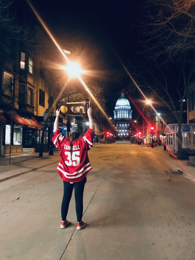 Kristen Campbell holds the national championship trophy in front of the Wisconsin State Capitol in Madison.