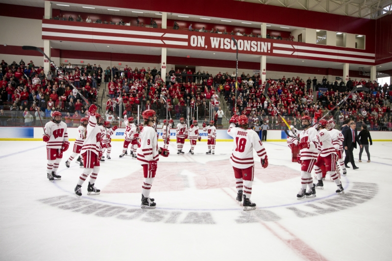 Wisconsin celebrates their 2019 NCAA Tournament quarterfinal game win over Syracuse with a stick salute to the crowd at LaBahn Arena. (Tom Lynn/Wisconsin Athletics)