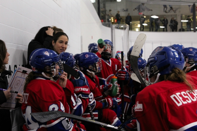 Les Canadiennes players gather around Caroline Ouellette and the coaching staff on the Montreal bench during a timeout. (Shanna Martin)