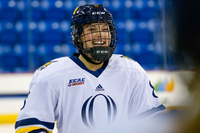 Lexie Adzija laughs with her teammate in the foreground during a break in Quinnipiac's game.