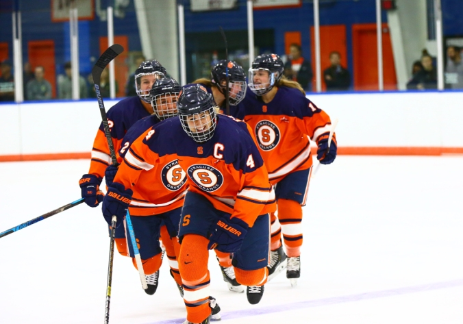 Syracuse captain and defender Lindsay Eastwood skates up to the bench to celebrate a goal with her teammates skating behind. (Syracuse University Athletics Department)