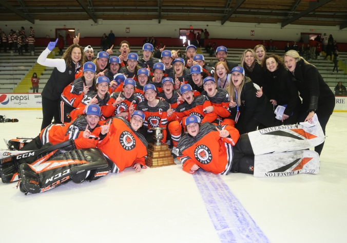 The Princeton women's hockey team gathers around the ECAC championship trophy at center ice for a celebratory photo, after winning the 2020 ECAC Tournament.