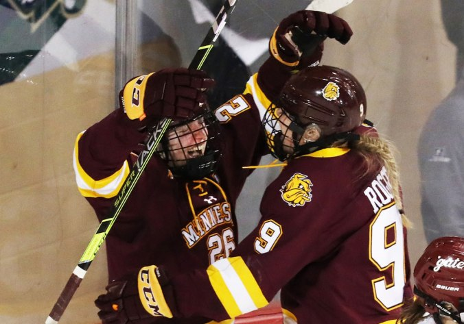 Minnesota Duluth defender Ashton Bell raises her stick and celebrates her overtime-winning goal with teammate Naomi Rogge in the 2021 NCAA Tournament quarterfinals.